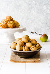 Different type of delicious cookies and a apple on white wooden table