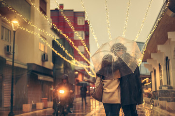 Couple in love on the street on a rainy day. Friends walking down the street