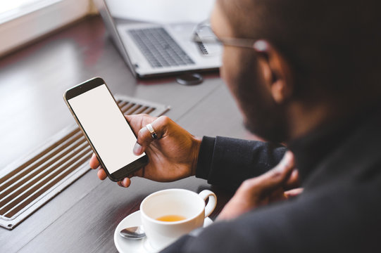 African American man sitting in a cafe, drinking coffee and working behind a mobile phone. Mock up screen