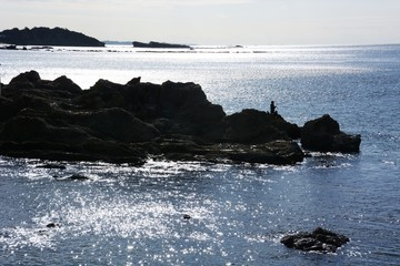 Shining of the sea surface and rocky silhouette