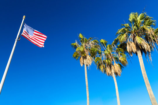 patriotism, independence day and summer holidays concept - american flag and palm trees over blue sky at venice beach, california