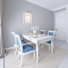 Luxurious dining table with white furniture and blue upholstery on the chairs.