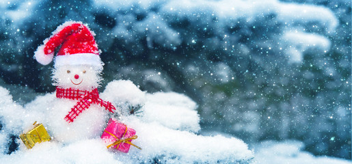Snowman with Christmas gifts and snowfall. Christmas background.