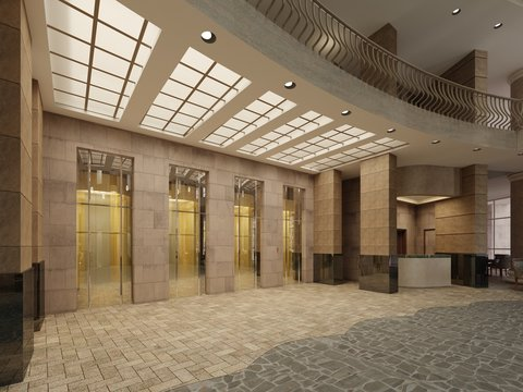 Brown marble and metal elevator hall in an hotel with a large columns. Built-in light in the ceiling.
