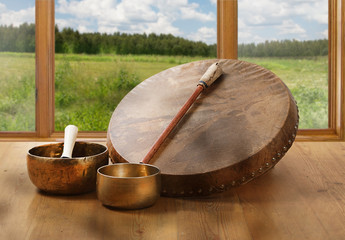 A still life of the shamanic drum and Tibetan singing bowls on a background of green fields and forests.