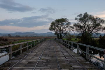 old wooden bridge over river late afternoon in Transylvania