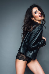 girl in leather jacket and shorts on a gray background laughing