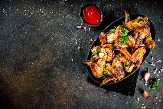 Baked grilled chicken wings on a black plate, with spices and ketchup sauce, on dark concrete background. Top view copy space