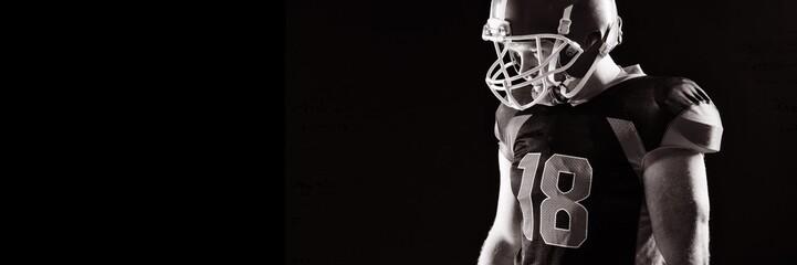 American football player in helmet standing against black