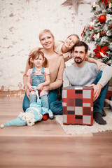 Photo of happy family sitting with box with gift at decorated New Year tree