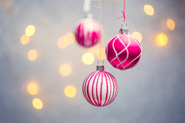 Picture of three Christmas pink balls with pattern on gray background with lights.