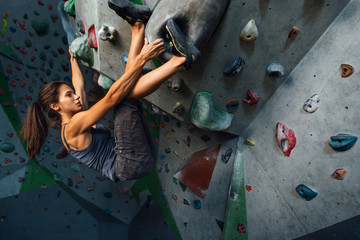 the girl hangs on the ledges climbing the wall in training room