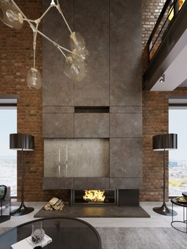 Large high concrete fireplace with built-in firebox with burning fire. Two black floor lamps.