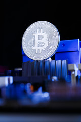 Photo of coin bitcoin and processor on blue background