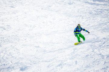 Photo of sports man snowboarding on snowy slope