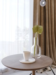 Decorative wooden round table with a glass vase and a green plant and a cup of coffee.