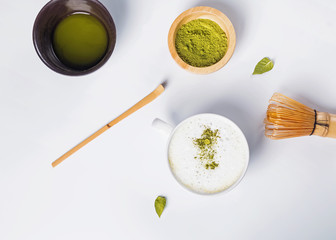 Wall Mural - Matcha latte in a cup, powder and tools for making tea on the white background,