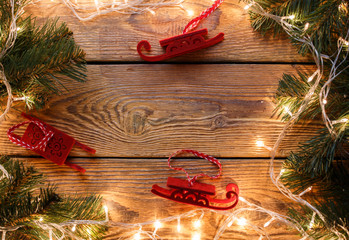 Photo on top of wooden table with burning garland, spruce branches, Christmas toys