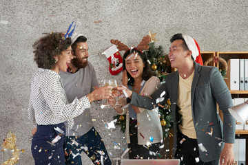 Laughing excited multi-ethnic coworkers toasting with champagne glasses under falling confetti