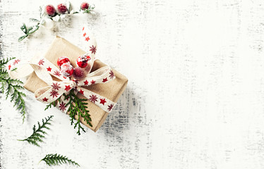 Christmas present wrapped in brown paper on white wooden background. Flatlay. Copy space