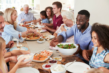 Group Of Multi-Generation Family And Friends Sitting Around Table And Enjoying Meal Wall mural