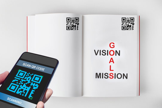 Hand holding smartphone with scanning QR code on book screen with words of goals, vision and mission on book, smart technology concept and QR codes link the book to the internet idea