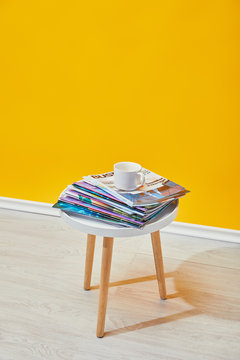 coffee table with journals and white cup near yellow wall