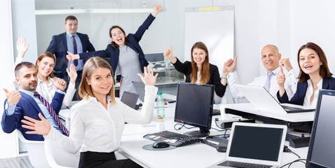 Group of happy business people emotionally gesturing and celebrating victory in modern office