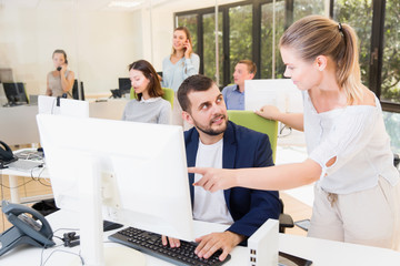 Successful businesswoman talking with guy colleague  at computer monitor