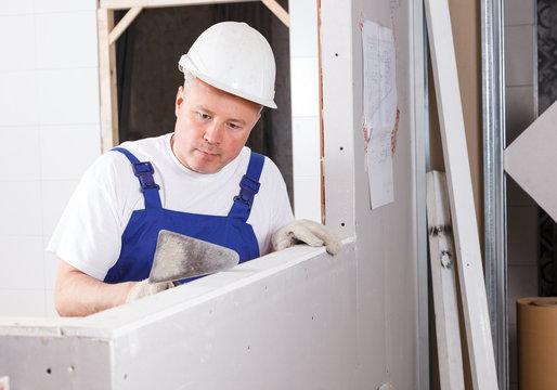 Worker mudding sheetrock wall