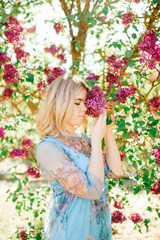 Portrait of young happy cheerful smiling positive blonde girl looking through branches with white and purple flowers in summer blooming park. Unusual lifestyle model relaxing and posing at nature.