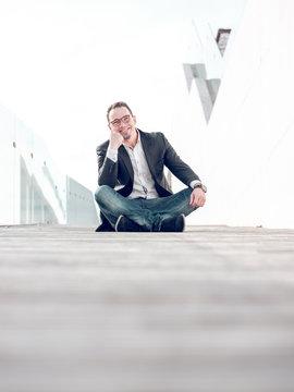 Cheerful businessman sitting near modern building