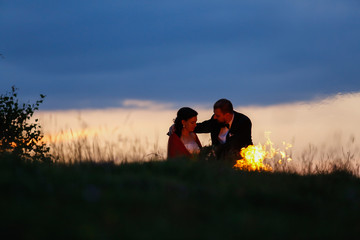 Beautiful wedding couple posing in nature with fire