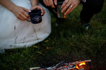 Bride holding groom's hand in front of fire in nature
