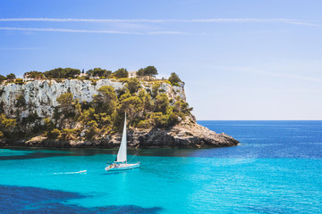 Beautiful bay with sailing boat yacht, Cala Galdana, Menorca island, Spain. Yachting, travel and active lifestyle concept