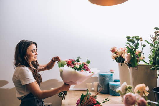 Young smiling brunette female business woman florist creating beautiful bouquet of colorful different flowers in modern interior floral shop. Side view