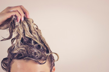 Funny woman pulls himself wet hair up. Close-up, space for text. Hair care concept