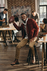 smiling african american casual businessman holding rugby ball with colleagues working behind in loft office