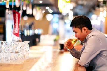 Young asian business man or freelancer sitting at night club bar drinking beer feeling thoughtful. Alcohol de-stressing for self medicating to relieve depressed after work concept with copy space.