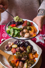Woman hand adds sauce to baked, roasted, grilled vegetables. Beetroot, carrot, mushrooms, pumpkin, brussels sprouts with avocado dip sauce. Vegan lunch, vegetarian dinner