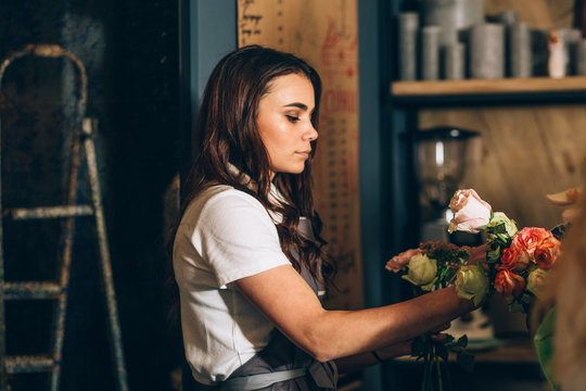 Young female business woman florist making beautiful bouquet of colorful roses in modern interior floral shop.