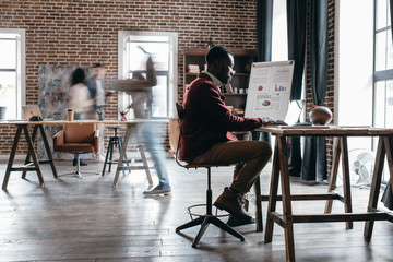 casual african american businessman working at desk with colleagues in motion blur in modern loft office