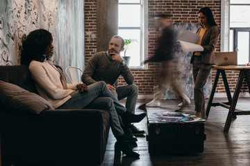 multiethnical couple of casual businesspeople sitting on couch with colleagues in motion blur in modern loft office
