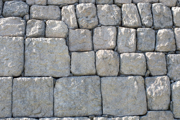 Stone wall is made from cubic hard grey rocks.
