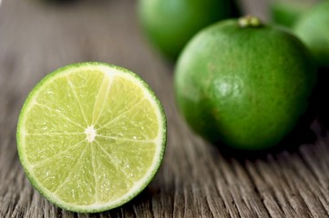 limes slices on wooden table. Detox diet, fresh lime Background, Close up shot, fruit macro photography