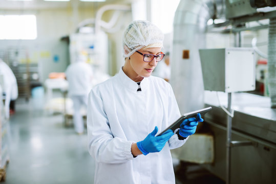 Female worker using tablet for controling products while standing in food factory.