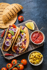 Tacos with chicken, vegetables and salsa sauce in tartilla on dark background