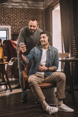 two smiling men using smartphone with colleagues working behind in modern loft office