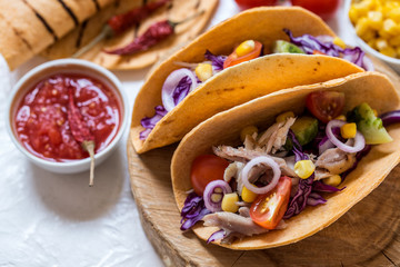 Tacos Mexican food with meat, fresh vegetables and salsa sauce on white background