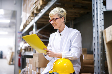 Female worker sitting on boxes and holding in hands folder with paperwork. Warehouse interior.